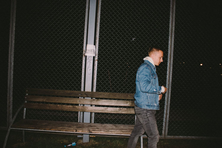 Side view of man walking by chainlink fence