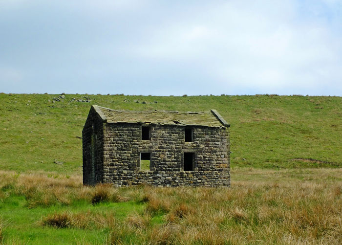 an old abandoned stone farmhouse in green pasture on high pennine moorland with bright blue sky Yorkshire Abandoned Buildings Architecture Building Building Exterior Built Structure Cloud - Sky Day Derelict Building Environment Field Grass History Land Landscape Nature No People Non-urban Scene Old Outdoors Plant Ruined Rural Scene Sky Wood - Material