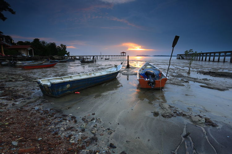 Boats Moored On Beach Against Sky During Sunset