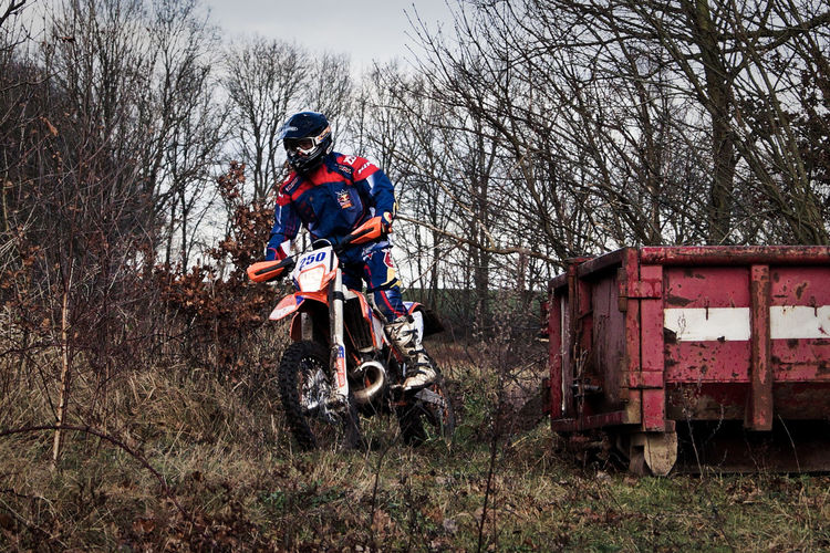 Person riding motocross on field against bare trees