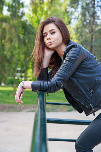 Portrait Of Woman Leaning On Railing In Park