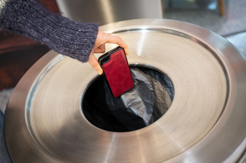 Cropped Hand Of Woman Putting Mobile Phone In Garbage Bin