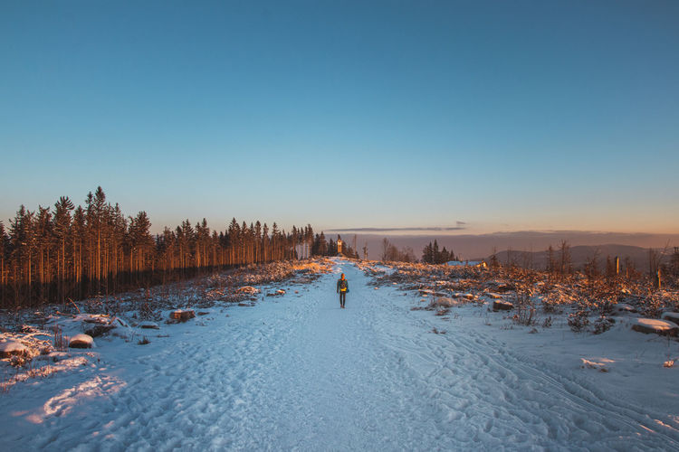 Man in winter clothes walking through a snowy road and a landscape without trees at sunrise