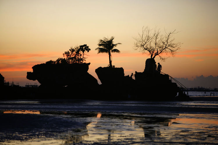 Silhouette rocks in sea against sky during sunset