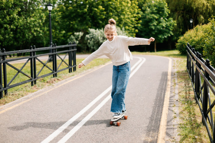 Cute blonde teenage girl is riding a skateboard in the city park.