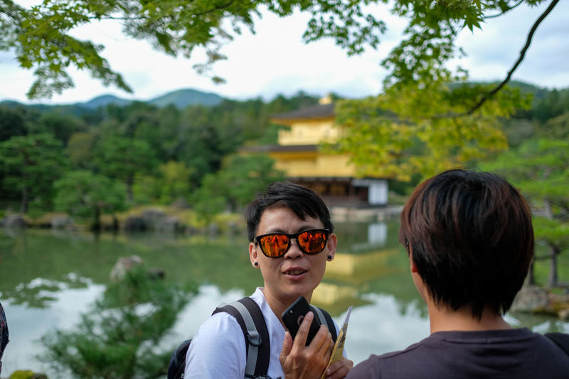 Kyoto Beauty In Nature Day Enjoyment Focus On Foreground Friendship Gold Green Color Holding Kinkaku-ji Leisure Activity Lifestyles Person Rear View Rural Scene Sunglasses Togetherness Tree Young Adult