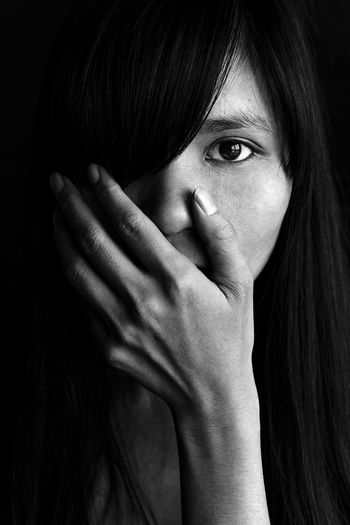 Close-up portrait of shocked young woman against black background