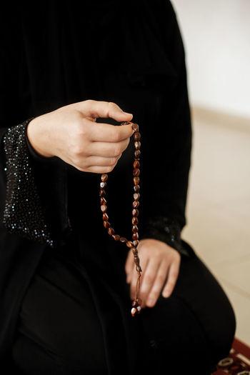 Prayer hands of a woman holding a rosary. ramadan kareem