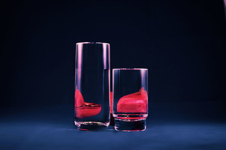 Black Background Studio Shot Indoors  No People Red Glass - Material Still Life Copy Space Transparent Close-up Blue Reflection Container Refreshment Pink Color Food And Drink Bottle Drink Glass Blue Background Minimalism Art Modern Water Illusion