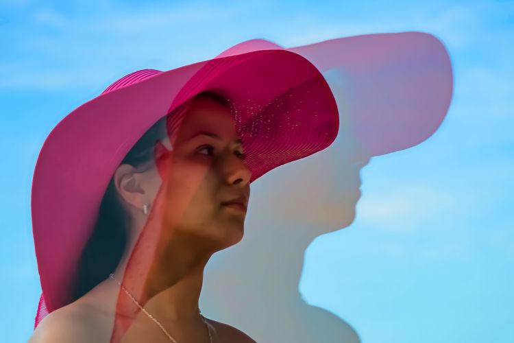 Close-up portrait of woman against blue sky
