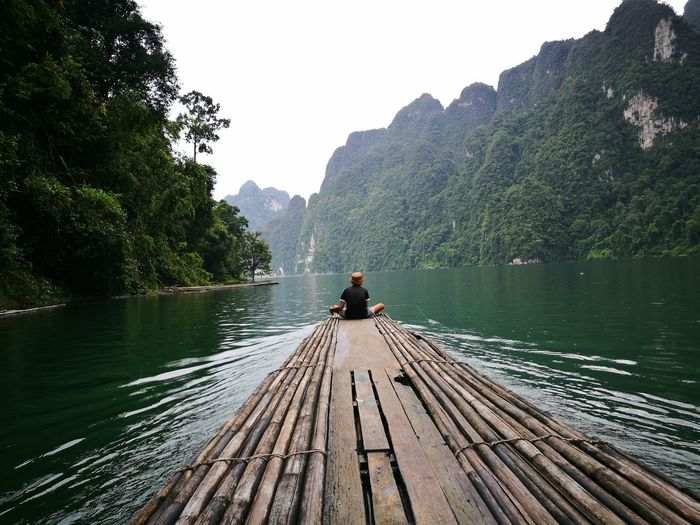 Man sitting on wooden raft at lake against sky