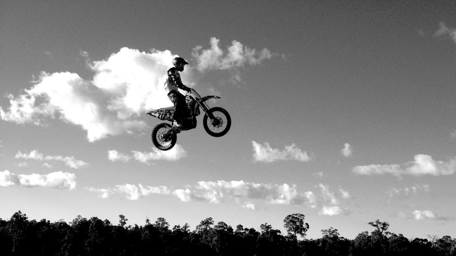 Low angle view of motocross rider performing stunt in mid-air