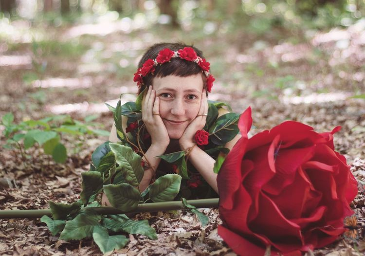 Portrait of smiling young woman with red flowers on land