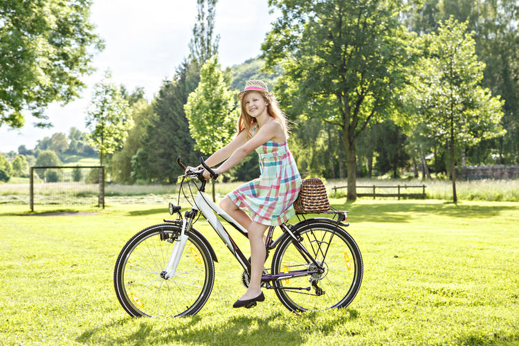 Portrait of woman riding bicycle on grass against trees