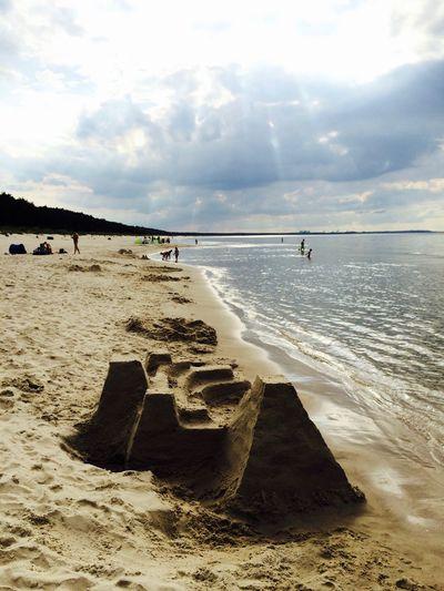 Sand castle at beach against sky