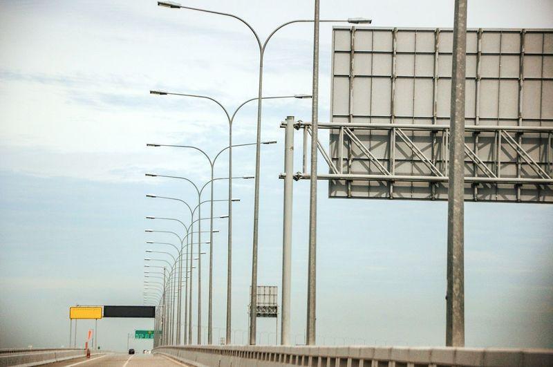Billboard and street lights on bridge against sky