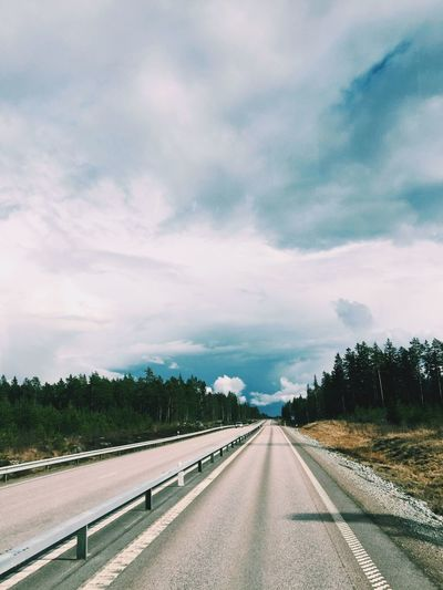 Highway Amidst Trees Against Cloudy Sky