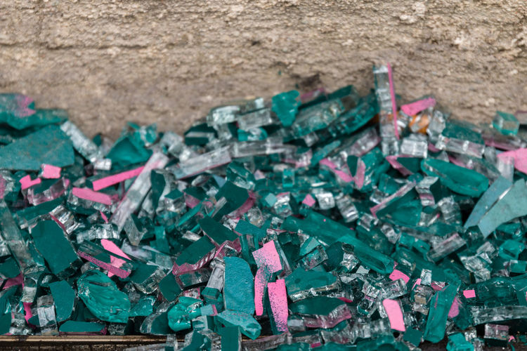 Close-up of green garbage against wall