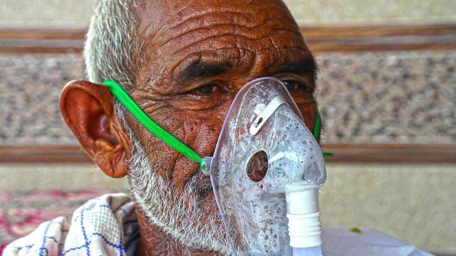 Close-up portrait of man wearing oxygen mask