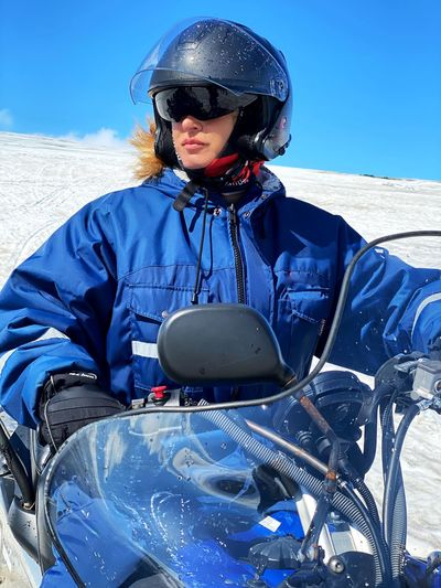 Mature woman wearing helmet riding motorcycle on snowy land
