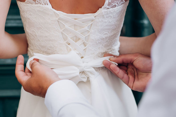 The groom tightens the corset to the bride on the wedding dress