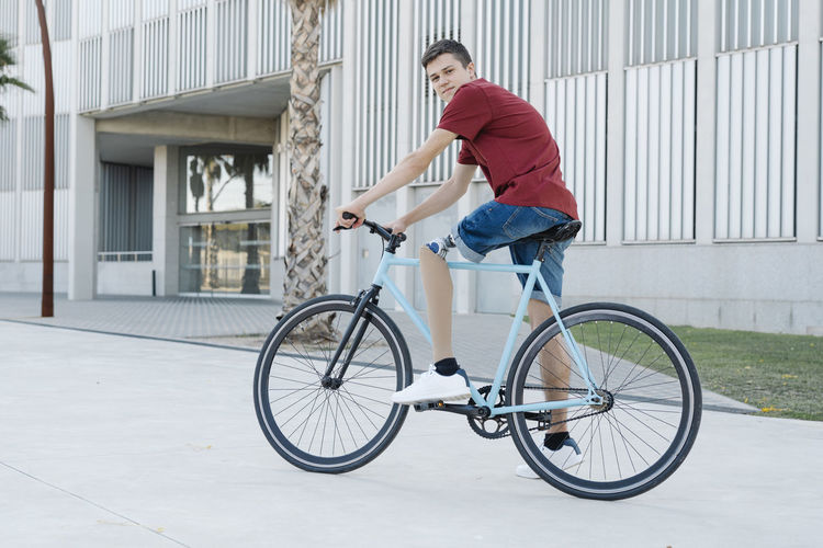 Side view of young man riding bicycle