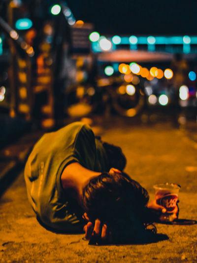 Close-up of man sitting on street at night
