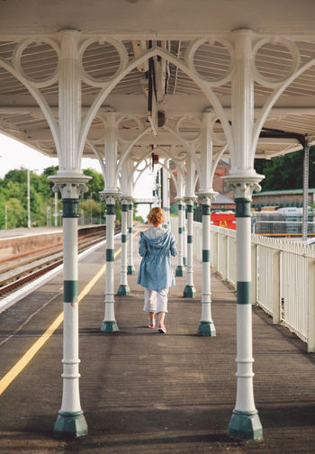 Arch Architectural Column Architecture Built Structure Casual Clothing Column Columns Curly Hair Day Full Length Girl Leisure Activity Lifestyles Platform Summer Sunset The Way Forward Tourism Train Station Train Station Platform Travel Destinations Walking Away Original Experiences Connected By Travel An Eye For Travel