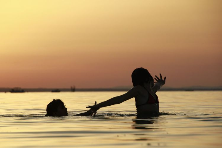Girls swimming in sea against sky during sunset