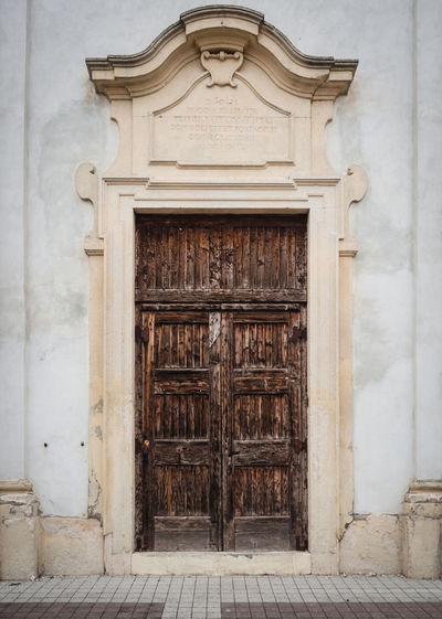 Peeling wooden door of an ancient Italian church. Ancient Antique Architecture Background Brown Building Cathedral Church Crack Detail Door Doorway Entrance Entrance Door Façade Gothic Medieval Old Ornamental Peel Peeling Retro Stone Style Texture Vintage Weathered White Wood Wooden