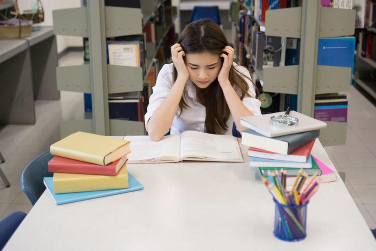 Tensed female student studying at table in library