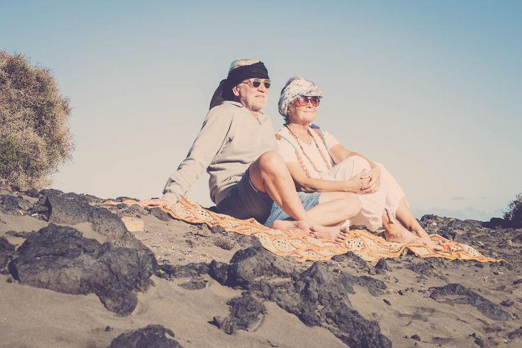 Happy Senior Couple Sitting At Beach Against Sky
