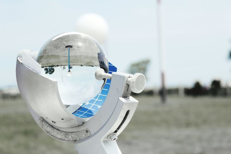 Close-up of crystal ball on equipment against sky
