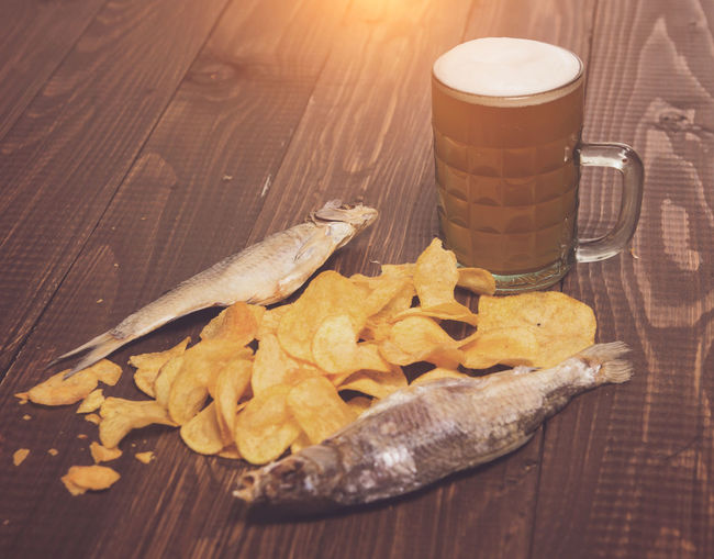 Close-up of beer glass with fish and chips on wooden table