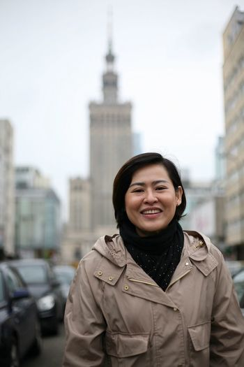 Portrait Of Cheerful Woman Standing Amidst Buildings In City