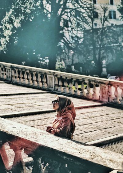 Side view of man sitting on railing against bridge