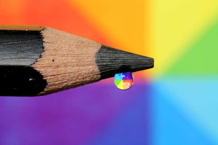 Close-up of multi colored water drop on pencil against umbrella