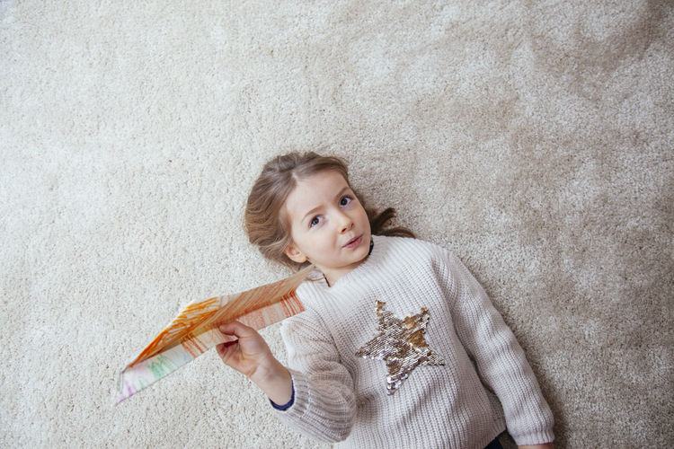 Portrait of girl holding paper airplane while lying on rug