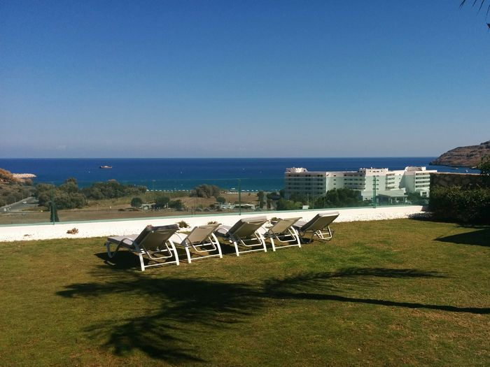 Empty chairs by calm blue sea against clear sky