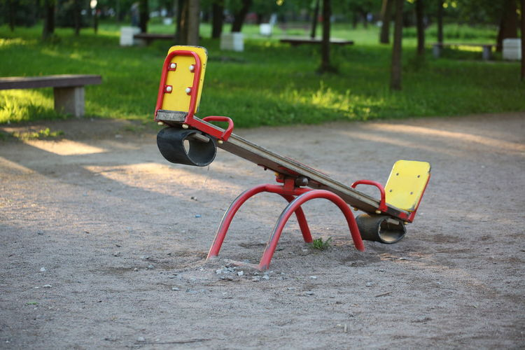 Absence Park No People Playground Day Park - Man Made Space Empty Nature Seesaw Focus On Foreground Metal Seat Outdoors Outdoor Play Equipment Yellow Grass Transportation Plant Red Park Bench