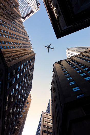 Directly below shot of airplane flying over buildings against sky