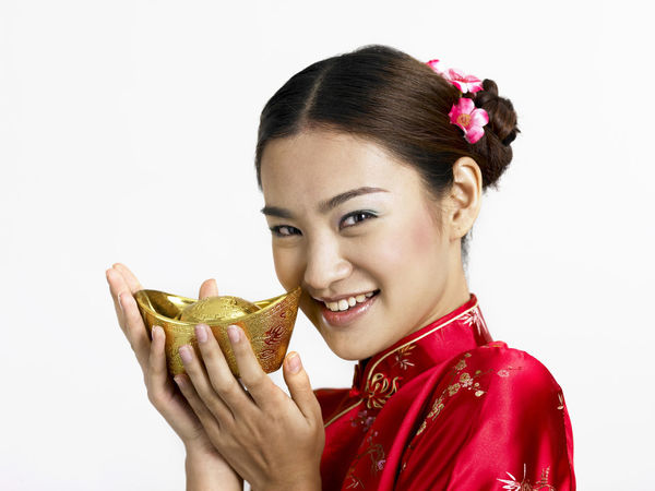 chinese woman holding gold ingot Gold Gong Xi Fa Cai New Year Prosperity Red Treasure Beautiful Woman Cheongsam Chinese New Year Fortune Hair Bun Happiness Headshot Heritage Holding Looking At Camera One Person People Portrait Qipao Smiling Studio Shot White Background Young Adult Young Women