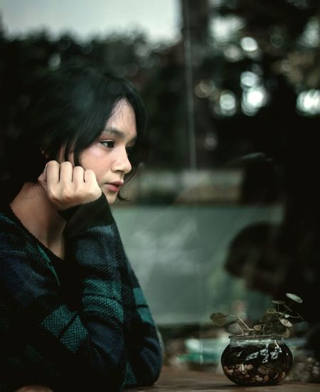 Young woman looking away while sitting at cafe