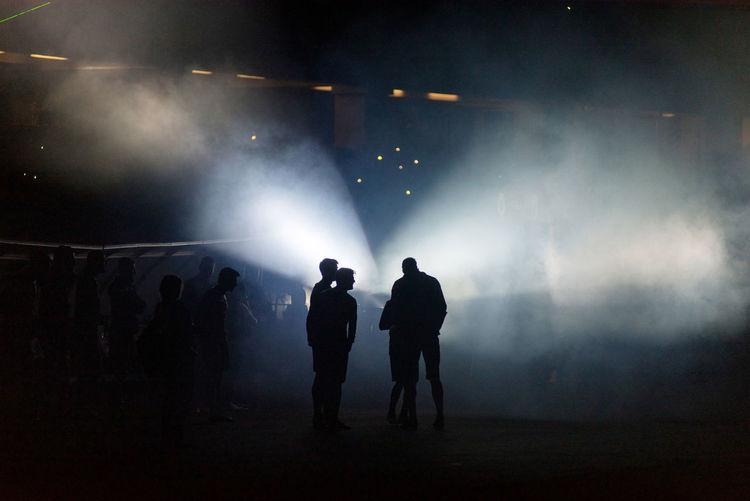 Silhouette people in illuminated stadium