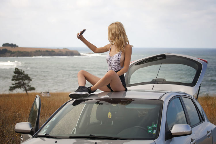 Seductive Young Woman Taking Selfie While Sitting On Car Roof Against Sky