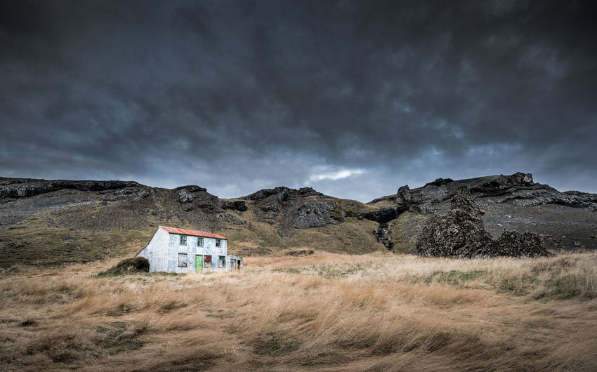 Built structure on landscape against cloudy sky