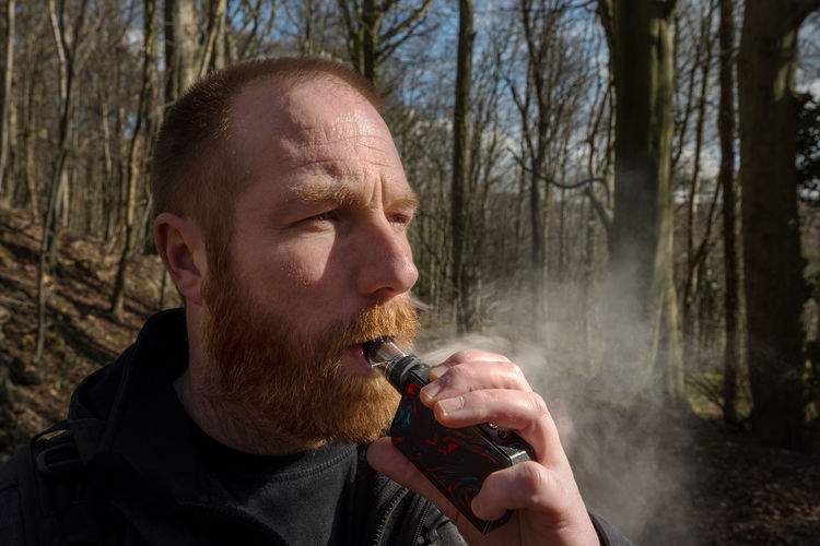Man Smoking Electronic Cigarette In Forest