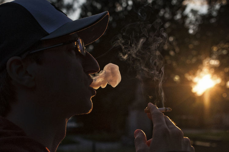 Side view of man smoking cigarette during sunset