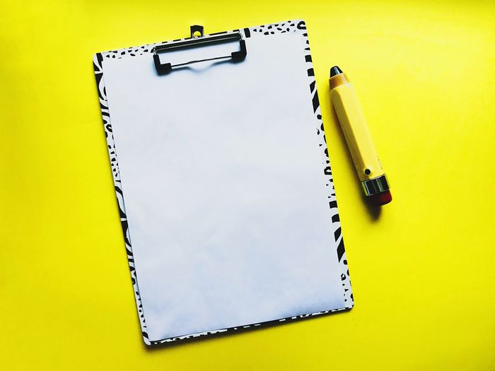 High angle view of pen on table against yellow background