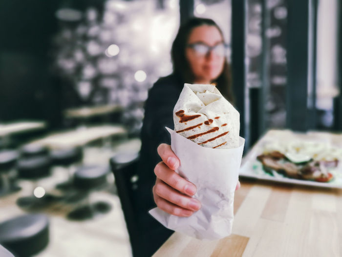 Woman giving wrap sandwich